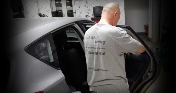 osoba w szarej koszulce stojąca przy otwartym samochodzie