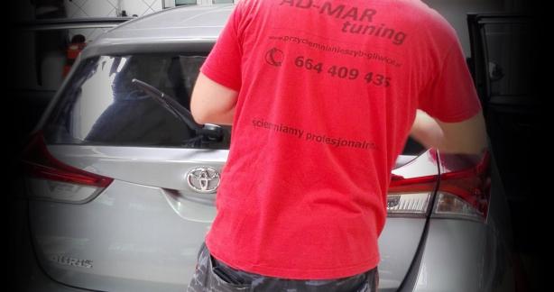 osoba w czerwonej koszulce stojąca za samochodem osobowym